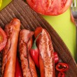 Delicious sausages with vegetables on plate on wooden table close-up — Stock Photo #32776737