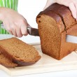 Stock Photo: Cutting bread on wooden board isolated on white