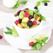 Fruit salad in cup on wooden table — Stock Photo