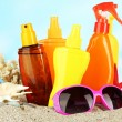 Bottles with suntan cream and sunglasses, on blue background — Stock Photo