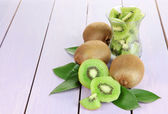 Ripe kiwi on purple wooden table close-up — Stock Photo