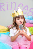 Little girl sitting on bed with microphone in room on grey wall background — Stock Photo