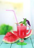 Copo de suco de melancia fresco, na mesa de madeira, no fundo brilhante — Foto Stock