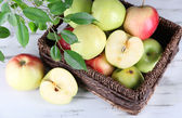 Juicy apples in basket on wooden table — Stock Photo
