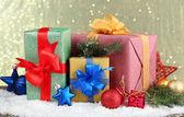 Regalos hermosos brillantes y una decoración de navidad, sobre fondo brillante — Foto de Stock