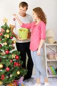 Lyckliga unga par nära julgran hemma — Stockfoto