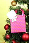 Gift on Christmas tree on color background — Stock Photo