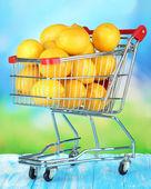 Ripe lemons in trolley on table on bright background — Zdjęcie stockowe