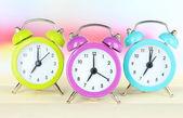 Colorful alarm clocks on table on light background — Stock Photo