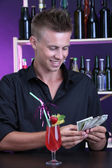 Portrait of handsome barman receiving tips from client — Stock Photo