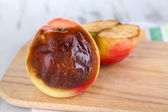 Rotten apples on wooden board on table — Stock Photo