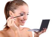 Beautiful girl paints eyelashes before small mirror isolated on white — Stock Photo
