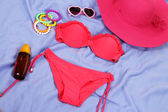 Strój kąpielowy i plaży przedmioty na fioletowym tle — Zdjęcie stockowe