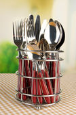 Knives, forks and spoons in metal stand on tablecloth on bright background — Stock Photo
