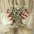 Female hands with wicker heart, close-up — Stock Photo #32780335