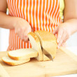 Woman slicing bread on chopping board, close up — Stock Photo #32780359