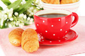 Tasty croissants and cup of coffee close-up — Stock Photo