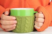 Cups with knitted things on it on wooden table close up — Stock Photo