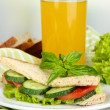 Composition with fruit juice and tasty sandwich with salami sausage and vegetables on color napkin, on wooden table, on bright background — Stock Photo