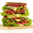 Huge sandwich on wooden board, isolated on white — Stock Photo