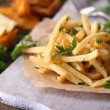 French fries on tracing paper on board on wooden table — Stock Photo