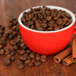 Coffee beans in cup on wooden background — Stock Photo #32935399