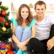Happy young couple near Christmas tree at home — Stock Photo #32936035