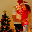 Happy young couple near Christmas tree at home — Stock Photo #32936065