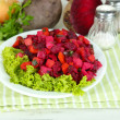 Beet salad on plate on napkin on wooden table — Stock Photo