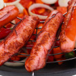 Delicious sausages in wok close-up background — Stock Photo