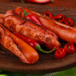Delicious sausages with vegetables on plate on wooden table close-up — Stock Photo
