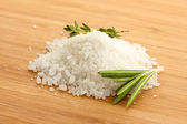 Salt with fresh rosemary and and thyme on wooden background — Stock Photo