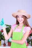 Beautiful girl gardener with flowers on grey background — Stock Photo