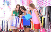 Three beautiful young woman in shop with shopping bags — Stock Photo
