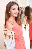 Beautiful girl with dresses near mirror — Stock Photo