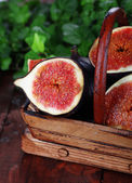 Ripe figs in basket on wooden table close-up — Stock Photo