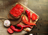 Composition with salsa sauce on bread,, red hot chili peppers and garlic, on sackcloth, on wooden background — Foto Stock