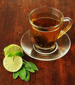 Transparent cup of green tea with lime on wooden background — Stockfoto
