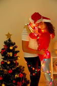 Happy young couple near Christmas tree at home — Foto Stock