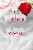Candles with printed sign I LOVE YOU,on white fabric background — Stock Photo
