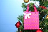 Regalo en el árbol de navidad sobre fondo de color — Foto de Stock