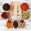 Various spices and herbs on wooden background — Stock Photo