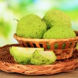 Osage Orange fruits (Maclurpomifera) in basket, on wooden table, on nature background — Stock Photo #33012765