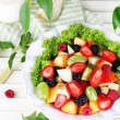 Fruit salad in plate on wooden table — Stock Photo