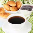 Tasty croissants and cup of coffee close-up — Stock Photo #33014361
