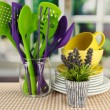 Plastic kitchen utensils in stand with clean dishes on tablecloth on bright background — Stock Photo #33014983