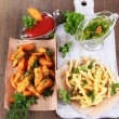 Stock Photo: French fries and home potatoes on tracing paper on board on wooden table