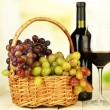 Ripe grapes in wicker basket, bottle and glass of wine, on light background — Stok Fotoğraf #33018471