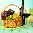 Ripe grapes in wicker basket, bottle and glass of wine, on bright background — Stock Photo #33018595