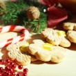 Cookies on ribbons with Christmas decorations on wooden table — Stock Photo #33019607